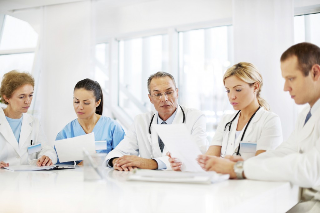 Doctors working together. They are sitting on a meeting and looking at the documents. The focus is on the mature man wearing glasses. [url=http://www.istockphoto.com/search/lightbox/9786662][img]http://dl.dropbox.com/u/40117171/medicine.jpg[/img][/url]